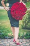 Mode som den härliga kvinnan bär den svarta klänningen, är den hållande stora buketten av 101 röda rosor Fotografering för Bildbyråer