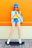 Mode som den nätta kalla flickan är, lyssnar till musik, och att använda en smartphone sitter på en skateboard över den färgrika  royaltyfria foton