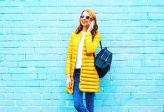 Mode som ler kvinnan, talar på en smartphone på tegelstenbakgrund fotografering för bildbyråer