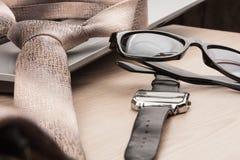 Mode und Geschäft Nahaufnahmesonnenbrille, Bindung und Uhr, auf einem Holztisch Stockfotos