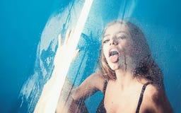 Mode und Schönheit Dusche und Hygienebadekur Fenster mit Wasser fällt vor Mädchen mit Make-up Regen-Tropfen an stockfotografie