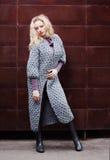 Mode und Schönheit Jugend und Art Ein schönes blondes Mädchen mit einem üppigen Haar führt einen modernen grauen Mantel von große Stockbilder