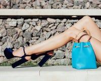 Mode Une fille avec de longues jambes dans des chaussures à talons hauts superbe-façonnées et un sac à main bleu d'été Photographie stock libre de droits