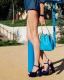 Mode Une fille avec de longues jambes posant dans des chaussures à talons hauts haut-façonnées et un sac à main bleu un jour chau Photos stock