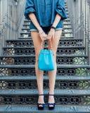 Mode Une fille avec de longues jambes posant dans les chaussures à talons hauts haut-façonnées et un sac à main bleu un jour chau Images libres de droits