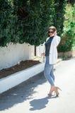Mode whilte Ausstattung der modischen sch?nen lachenden Frau in der Sonnenbrille, die auf dem wei?en Wandhintergrund aufwirft lizenzfreie stockfotografie