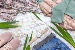 Mode women' s-kläder, moderiktig tillbehör för tropiska sidor ställde in på beige vit marmorbakgrund Stilfull tillf?llig dr? arkivbilder