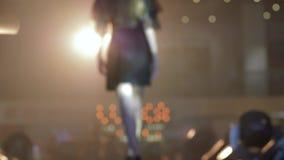 Modeaftonhändelsen, konturcatwalkmodell in i kappan går på podiet i panelljus i unfocused under presentation stock video