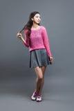 Modeasiatung flicka Stående på grå färger Arkivbilder