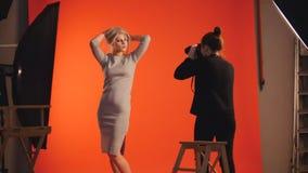 Modebühne hinter dem vorhang: blondes Mädchenmodell und Fotograf - Fotosession im Studio Stockfotografie
