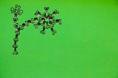 Modebeståndsdelar: metallkrok och stängande ögon på en grön bakgrund arkivbilder