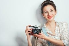 Modeblick, recht k?hles Modell der jungen Frau mit der Retro- Kamera, die in der Denimkleidung aufwirft auf wei?er Wand tr?gt Aus stockfotos