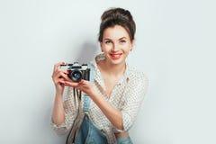 Modeblick, recht k?hles Modell der jungen Frau mit der Retro- Kamera, die in der Denimkleidung aufwirft auf wei?er Wand tr?gt Aus lizenzfreies stockbild