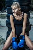 Modeboxarekvinna i en svart sportswear och med blåa boxninghandskar Fotografering för Bildbyråer