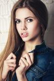 Modecloseupståenden av den härliga blonda flickan i jeans bär Arkivbild