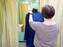 Modedesigner, der auf Mannequin schaut stockfotos