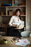 Modedesigner der erwachsenen Frau, der in einem gemütlichen Büro nahe seinem steht Stockbilder