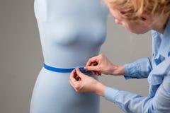 Modedesigner, der mit blauer Schneiderattrappe in ihrer Werkstatt arbeitet Lizenzfreies Stockbild