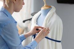 Modedesigner, der mit blauer Schneiderattrappe in ihrer Werkstatt arbeitet Stockfotografie