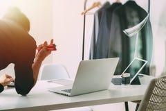 Modedesigner, der mit Handy arbeitet und Laptop mit verwendet Lizenzfreie Stockbilder