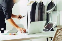 Modedesigner, der mit Handy arbeitet und Laptop mit verwendet Stockbild