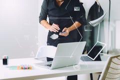 Modedesigner, der mit Handy arbeitet und Laptop mit verwendet Stockfotos