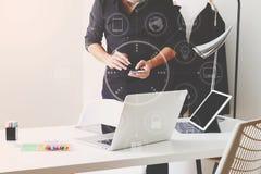 Modedesigner, der mit Handy arbeitet und Laptop mit verwendet Stockbilder