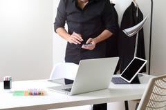 Modedesigner, der mit Handy arbeitet und Laptop mit verwendet Lizenzfreie Stockfotos