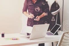 Modedesigner, der mit Handy arbeitet und Laptop mit verwendet Stockfoto