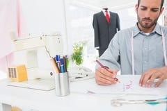 Modedesigner, der an seinen Designen im Studio arbeitet Lizenzfreies Stockbild