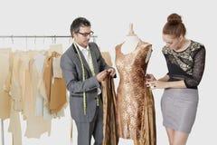 Modedesigner, die zusammen an einer Ausstattung im Entwurfsstudio arbeiten Lizenzfreie Stockfotografie