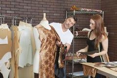 Modedesigner, die zusammen an einer Ausstattung im Entwurfsstudio arbeiten stockbilder