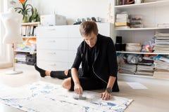 Modedesigner mit dem Stoff, der Kleid am Studio herstellt lizenzfreies stockbild