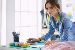 Modedesignerfrau, die an ihren Designen im Studio arbeitet lizenzfreies stockbild