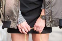 Modedetails junge stilvolle Frau, die ihre Tasche mit einer goldenen Kette hält tragender goldener Schmuck, graue warme Strickjac Lizenzfreies Stockfoto