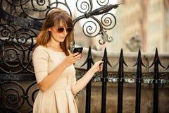 Modeflicka med den smarta telefonen utomhus Royaltyfri Foto