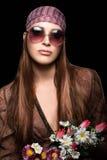 Modeflicka med hippiestil som rymmer en bukett av blommor Royaltyfria Bilder