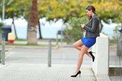 Modeflicka med länge perfekta ben genom att använda telefonen Royaltyfri Foto