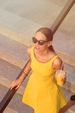 Modeflicka som går med den orange coctailen Royaltyfri Bild