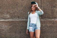 Modeflicka som poserar nära betongväggen Arkivbilder