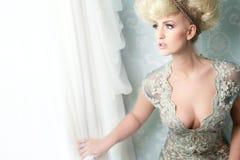Modeflicka som ser ut ur fönster Royaltyfri Bild