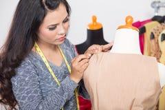 Modeformgivare eller skräddare som arbetar på en design eller ett utkast, measuri royaltyfri foto