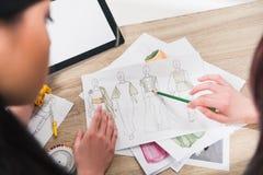 Modeformgivare som arbetar med ritningar av modeller på tabellen Arkivbild