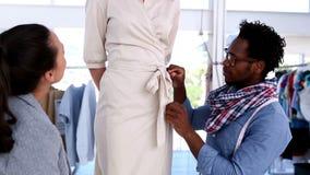 Modeformgivare som arbetar på bältet av en klänning lager videofilmer