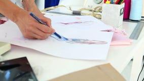 Modeformgivare som skissar en klänningdesign arkivfilmer
