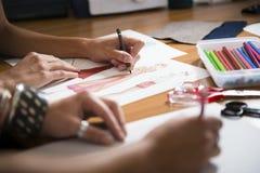 Modeformgivare som tecknar den nya klänningen i studio Arkivfoton