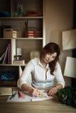 Modeformgivaren för den vuxna kvinnlign drar en skissa i ett hemtrevligt kontor Royaltyfri Fotografi