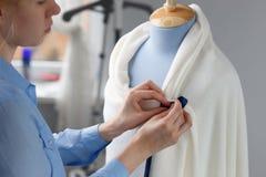 Modeformgivaren som arbetar med blått, anpassar attrappen i hennes seminarium Royaltyfria Bilder
