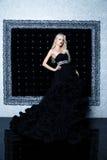 Modefors av den härliga blonda kvinnan i en lång svart klänning Arkivbild