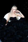Modefors av den härliga blonda kvinnan i en lång svart klänning Arkivfoton